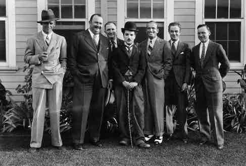 Charlie Chaplin, dressed as The Tramp, standing outdoors with Fairbanks Jr, bandleader Paul Whiteman, and with Fairbanks Sr third from the right.