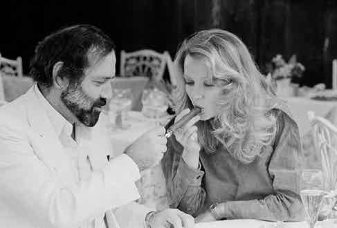 French director Jean Yanne lights a cigar for his partner, actress Mimi Coutelier.