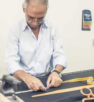Antonio Ambrosi checks the pattern of a pair of trousers.