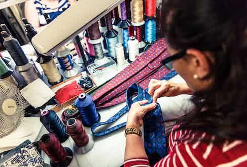 A seamstress slipstitches a tie.