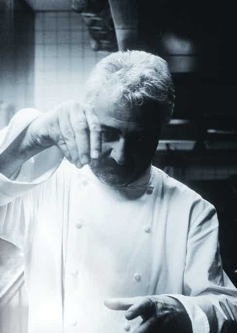 Legendary chef Guy Savoy in his kitchen adding his final touch.