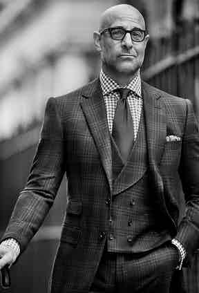 Charcoal-grey large-checked three-piece suit with shawl lapel double-breasted waistcoat, grey and white check cotton shirt and onyx-black silk twill tie, all Cifonelli. Charcoal-grey and ivory silk spotted pocket handkerchief, property of The Rake; black acetate spectacles, E.B. Meyrowitz, property of Stanley Tucci.