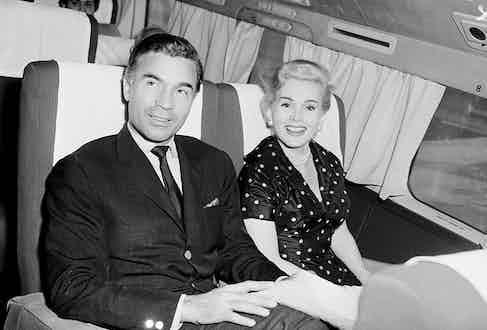 Porfirio Rubirosa and the lovely actress Zsa Zsa Gabor smile as they pass through Miami en route to the West Coast, circa 1954.