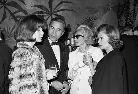 The New York café society congregates at El Morocco in December 1964 for the official reopening of the famed supper club under the ownership of Englishman John Mills. Among those present were Porfirio Rubirosa and (from left) his French actress wife Odile Rodin, Mrs Denniston Slater and actress Constance Bennett.