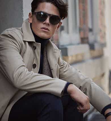 Sand-brown cotton raincoat, Aquascutum; brown herringbone wool single-breasted sport coat, navy wool trousers, both Brunello Cucinelli; teal-blue cashmere roll-neck jumper, Chester Barrie; brown tortoiseshell acetate sunglasses, Oliver Goldsmith; Arceau Automatique gentleman's timepiece in rose gold with black alligator-leather strap, Hermès.