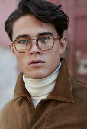 Caramel suede field jacket, Cerruti 1881; Cream cashmere roll-neck jumper, John Smedley; soft tiger-stripe rust- brown eye frames, Persol.
