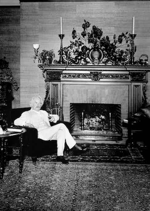 American author and humorist Samuel Langhorne Clemens - better known as Mark Twain - enjoying a tipple in his library (1909).