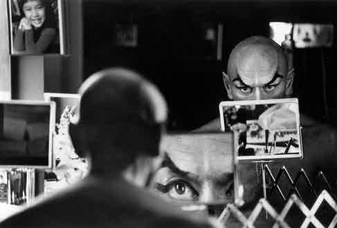 Yul Brynner does a double check on his make-up with a magnifying mirror.