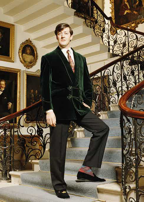 English comedian Stephen Fry looking rakish in a lounge coat and velvet slippers.