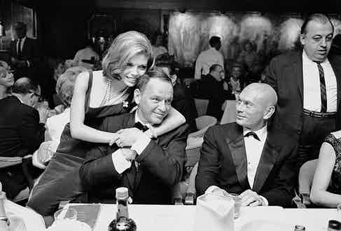 1965: Frank Sinatra getting affectionate hug from daughter Nancy as actor Yul Brynner looks on