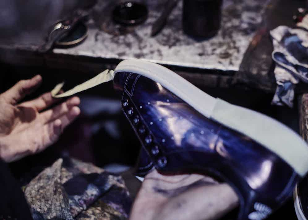 Removing the tape which ensures that the soles remain unblemished during the painting process.