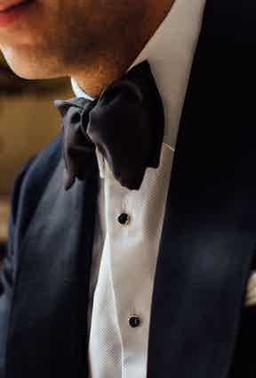 """Jonathan's ivory spun silk scarf, silver and onyx dress studs and links, and his moiré bow tie are all from Budd Shirtmakers. """"The staff at Budd truly understand formalwear and offer a wonderful service,"""" he says. """"These studs were apparently made for Budd by a semi-retired gentleman who's a one-man-band silversmith in Derbyshire. It's nice to know that when we invest in such things we help to keep these artisanal traditions alive in the UK."""""""