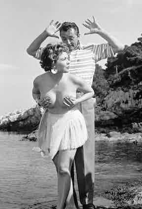 British actress Simone Silva photographed topless with Robert Mitchum on the Lérins Islands.
