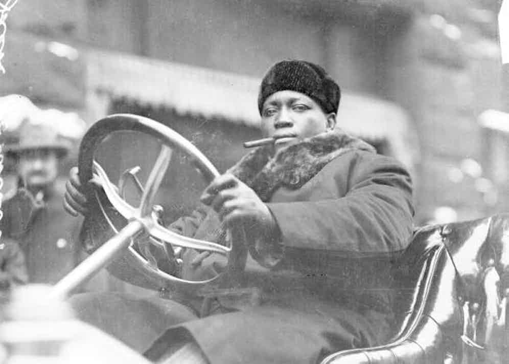 1910, Jack Johnson smoking a cigar while driving an automobile in Chicago, Illinois. Photo by Chicago History Museum.