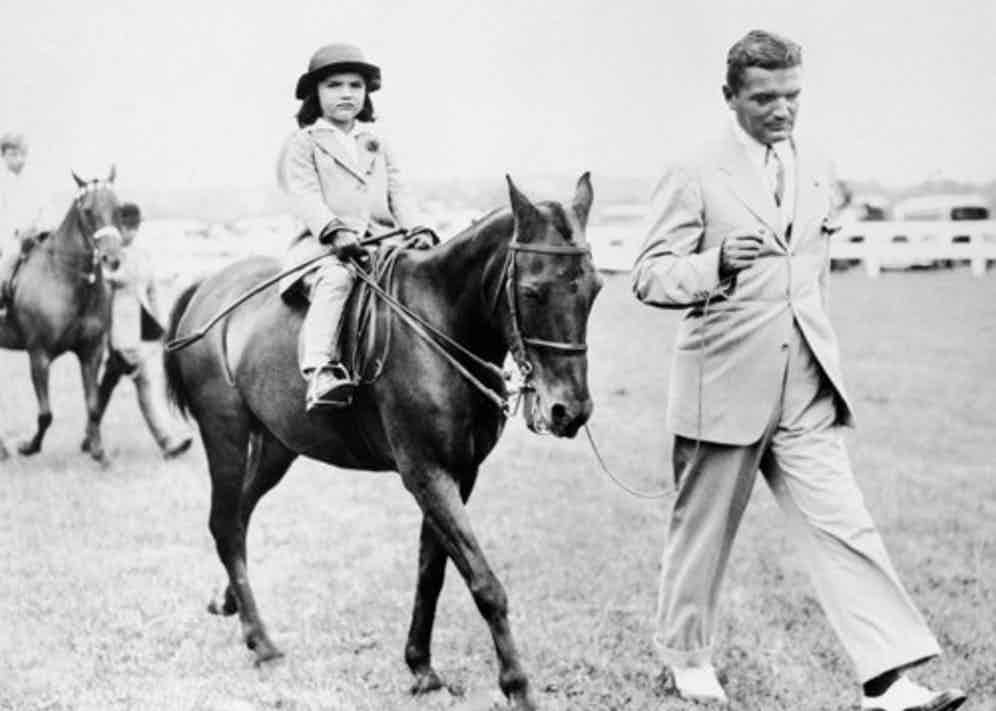 Bouvier keeping a five-year-old Jackie company during her riding lesson, 1934.