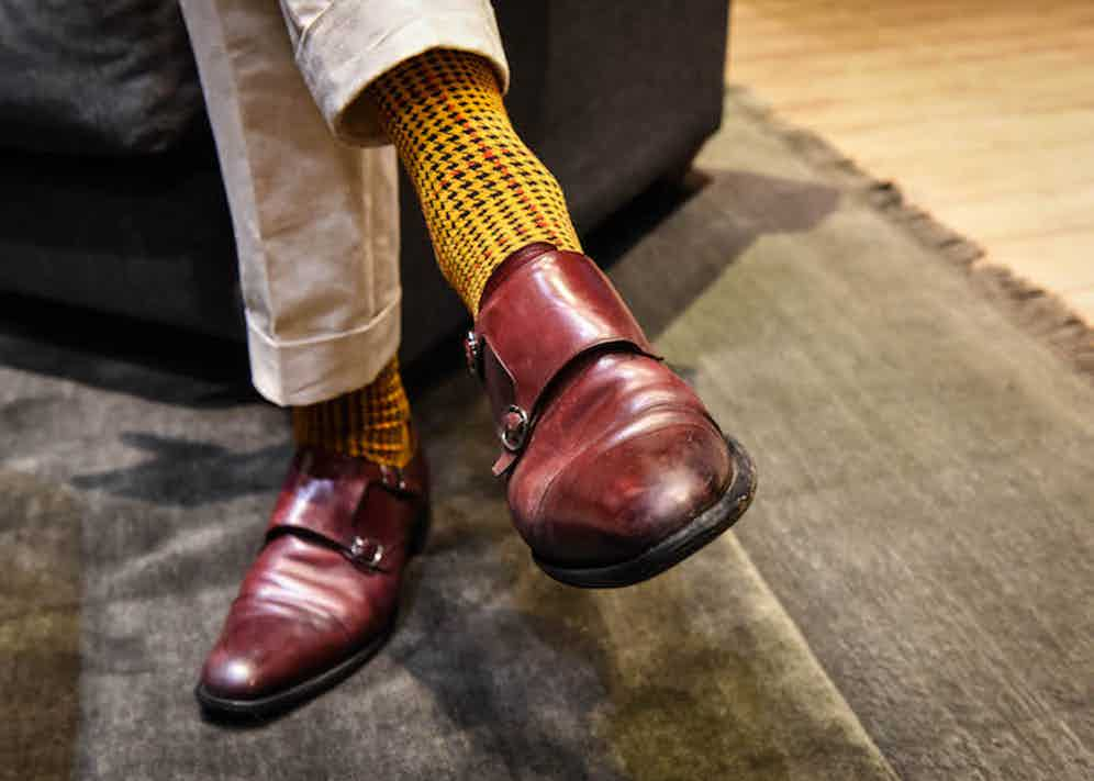 """Joe's socks are his own design – the result of a unique collaboration with the London Sock Co., a houndstooth pattern was chosen for its British quality, and the colours used for same reason: """"they are inspired by the colours of British military dress"""" he explains, """"the burnt orange comes from the gold of the epaulettes and the pillar-box red from the tunics of the Household Cavalry."""""""