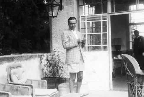 American composer Cole Porter (1892 - 1964), dressed in shorts and a checkered jacket, relaxes on a patio, Mittersill, Austria, 1937. (Photo by Pictures Inc./The LIFE Picture Collection/Getty Images)