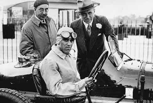 Tazio Nuvolari sits in the Earl of Howe's Bugatti while the dapper Earllooks on, accompanied by  Hugh McConnell