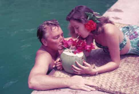 Teddy Stauffer and a friend share a drink from a coconut shell, Acapulco, Mexico, 1952 (Photoraph by Slim Aarons)
