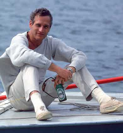 Paul Newman sitting on the prow of a boat in a casual ensemble including white plimsolls and a soft grey sweater in Florida Keys, 1967.