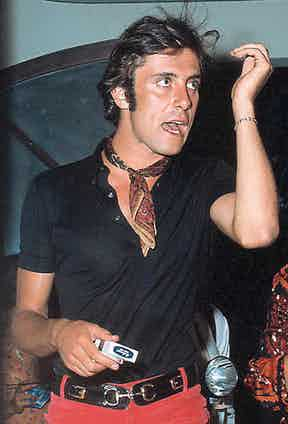 Gigi Rizzi pairs a dark, unbuttoned shirt with a brightly covered neckerchief in Saint Tropez, 1968.