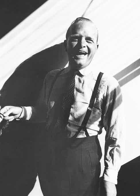 Writer Truman Capote standing in a sunbeam, laughing, dressed in a striped dress shirt, tie and pants with suspenders, 1965. Image by © Condé Nast Archive/Corbis.