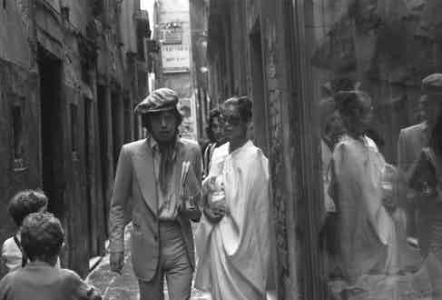 Mick Jagger, wearing a suit and a cap, walking with his wife Bianca Jagger, wearing sunglasses, in a calle, Venice, 1971. Photograph by Archivio Cameraphoto Epoche/Getty Images.