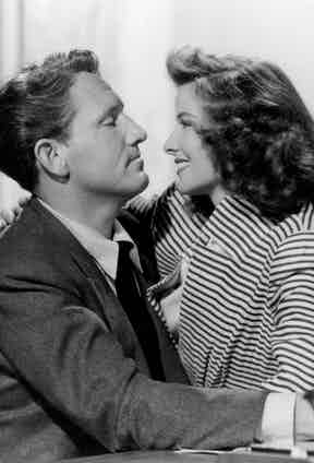 Katharine Hepburn sitting on Spencer Tracy's lap in his office in a scene from the film 'Woman Of The Year', 1942. Photo by Metro-Goldwyn-Mayer/Getty Images.