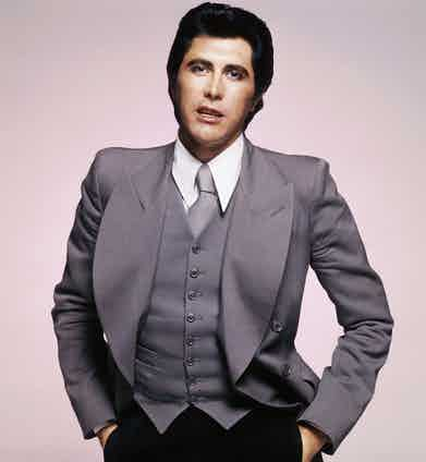 In a grey jacket with broad lapels, circa 1976. Photo by Terry O'Neill/Hulton Archive/Getty Images.