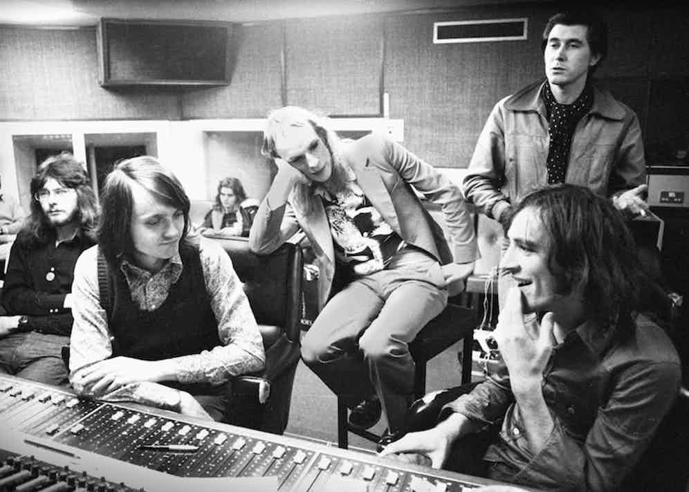 Roxy Music in the control room of a London recording studio in 1972 listening to a playback. Andy MacKay is far left, Paul Thompson is back centre on a sofa, Brian Eno is centre on a high stool, Bryan Ferry stands back right, record producer Chris Thomas is front right, sitting at the mixing desk. Photo by Gijsbert Hanekroot/Redferns.