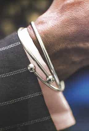 These bracelets have deep personal significance for Dennis. Civil rights activist Kimako Baraka made him the first. The other was made during his time in Nigeria with Fela Kuti. Dennis says 'they represent African Africa and American Africa', and their interlinking serves as a reminder of Dennis's identity.