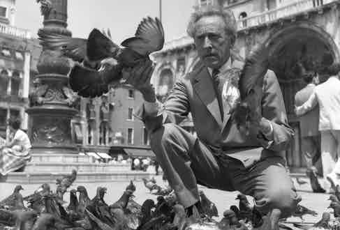 Jean Cocteau wearing a plaid suit and a fancy tie, crouched in St. Mark Square while feeding pigeons, Venice 1956. Photo by Archivio Cameraphoto Epoche/Getty Images.