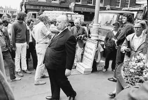 English film director Alfred Hitchcock during location filming in Covent Garden, London, for his film 'Frenzy', 1971. The set is dressed with a newspaper sign (right) reading: 'Another Necktie Strangling'. Photo by Jack Kay/Daily Express/Hulton Archive/Getty Images.