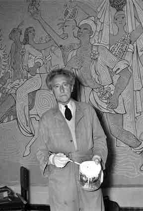 Jean Cocteau in front of a fresco he painted inside the wedding hall of Menton (southern France), 1957. Photograoh by Jean Meunire/AFP/Getty Images.