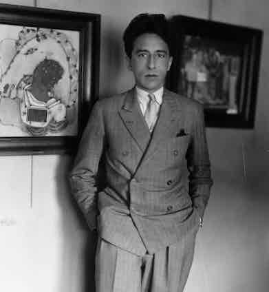 Jean Cocteau standing next to one of his paintings (left). Photo by Sasha/Getty Images.
