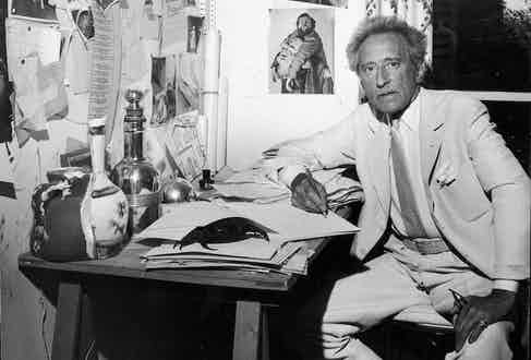 Jean Cocteau sitting at a desk. The wall holds many clippings belonging to American friend Francine Weisweller, where he was living. Photo by Leo Rosenthal/Pix Inc./The LIFE Images Collection/Getty Images.