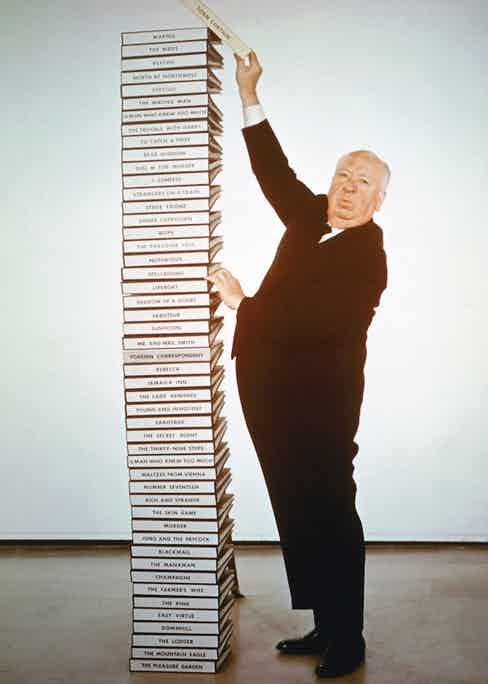 English film director Alfred Hitchcock  adds the script of his latest film 'Torn Curtain' to a pile of scripts representing his career from 1925 to 1966. Photo by Silver Screen Collection/Hulton Archive/Getty Images.