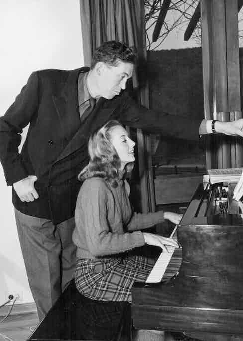 Director John Huston turning the pages of sheet music for his wife, actress Evelyn Keyes, as she plays the piano, 1948. Photo by Pictorial Parade/Archive Photos/Getty Images.
