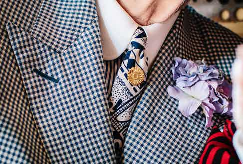 """Nothing George wears matches – but somehow it all works, the bold check cloth of his suit balanced by a delicate flower in his lapel. """"I've always loved flowers – it's something that's in my family, I suppose. My grandfather used to have flower stalls all over London – Covent Garden, Spitalfields..."""""""