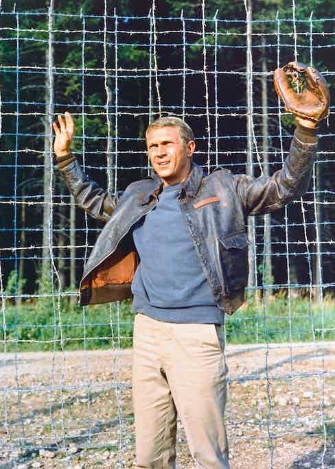 Steve McQueen wearing a leather jacket and a baseball glove, with his hands held up in submission, in a publicity still issued for the film, 'The Great Escape', 1963. Photo by Silver Screen Collection/Getty Images.
