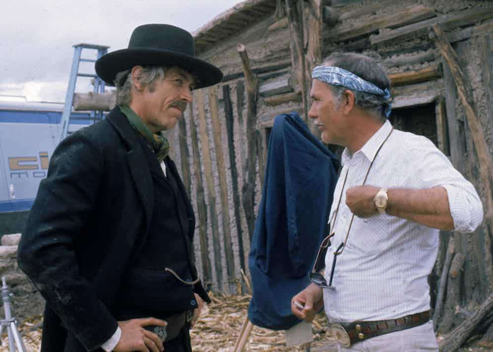 James Coburn in costume and Sam Peckinpah on the set of the film, 'Pat Garrett and Billy the Kid', USA, 1973. Photo by Silver Screen Collection/Getty Images.