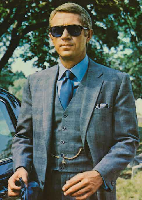 Steve McQueen wearing sunglasses with a grey suit, a blue shirt and dark blue tie in a publicity image issued for the film, 'The Thomas Crown Affair', 1968. (Photo by Silver Screen Collection/Getty Images)
