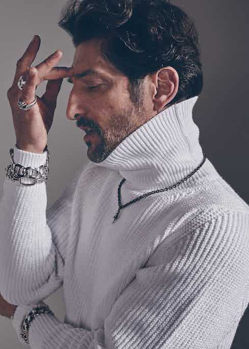 White ribbed cotton roll-neck, Bally; silver large link bracelet and silver oval link bracelet, both  Pomellato 67; oxidised silver chain, dagger pendant, chunky silver chain bracelet, large silver etched skull ring and large silver cross with pavè diamond ring, all Chrome Hearts.