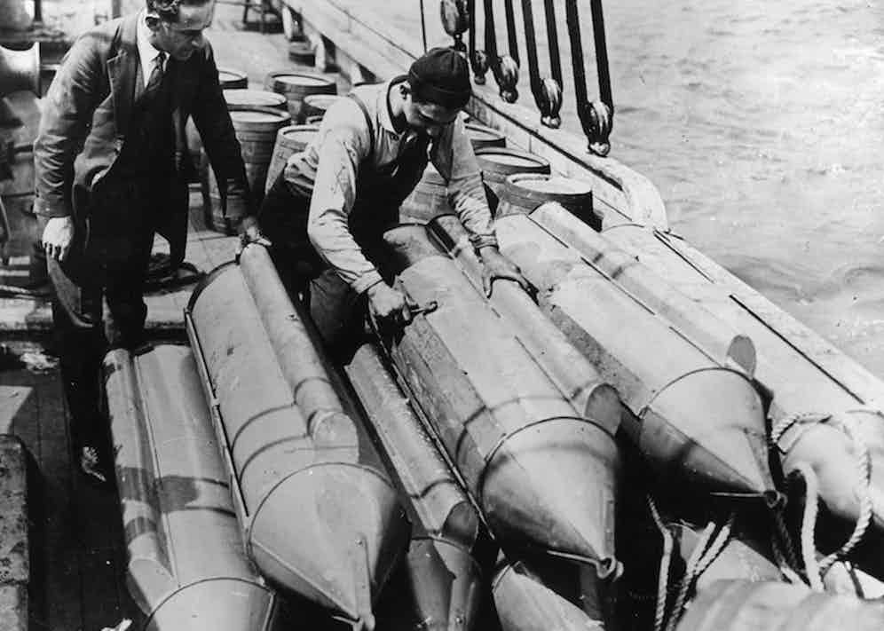 US customs officials examine steel torpodoes on the schooner 'Rosie'. The torpodoes are filled with whisky and  designed to be towed undetected through the water to beat Prohibition in the USA.  Photo by Topical Press Agency/Getty Images.
