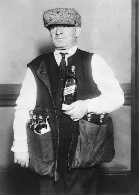 January 1923:  A revenue agent wearing a waistcoat designed to hide whisky during the prohibition era in America.  Photo by Topical Press Agency/Getty Images.