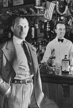 The 21 Club's Jack Kriendler relaxing at the bar with a drink, a bartender holding a bottle on the other side of the bar.  Photo by Eric Schaal/The LIFE Picture Collection/Getty Images.