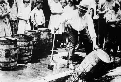 circa 1920:  A man destroying barrels of alcohol during prohibition in America.  Photo by General Photographic Agency/Getty Images.