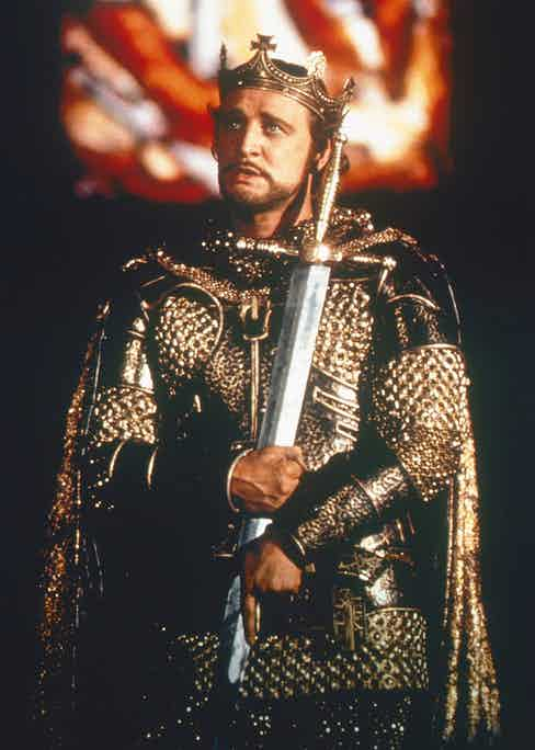 Richard Harris wearing a crown and an ornate suit of armour, holding a sword to his chest, in a publicity still issued for the film, 'Camelot', 1967. The musical starred Harris as 'King Arthur'. Photo by Silver Screen Collection/Getty Images.