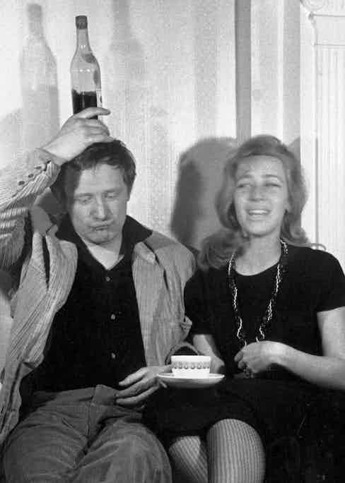 Richard Harris balances a bottle on his head, next to his wife Elizabeth. Photo by Evening Standard/Getty Images.