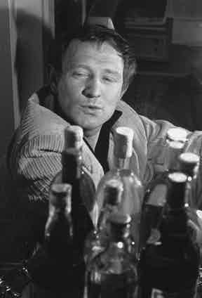 Richard Harris surveys an impressive collection of bottles, perhaps considering his next choice. Photo by Evening Standard/Getty Images.
